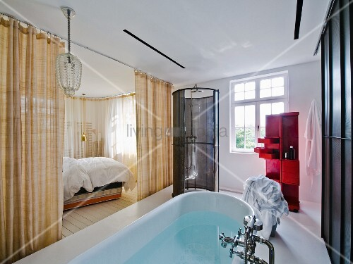 Free-standing bathtub in ensuite bathroom with view into bedroom through open curtains