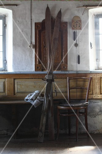 Vintage skis next to Thonet chair in sparsely-furnished farmhouse parlour