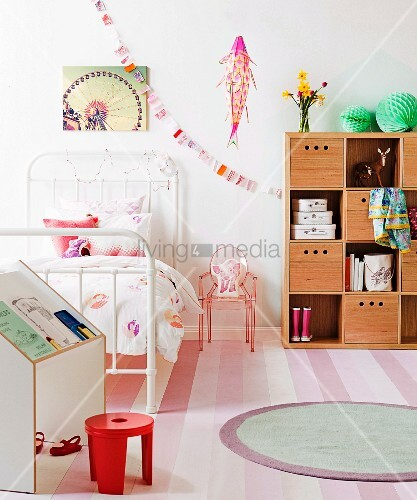 Simple writing desk, red stool, white metal bed, small plastic chair, wooden storage boxes on shelves and round rug on striped carpet