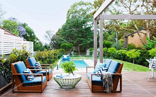Comfortable outdoor furniture with blue cushions on terrace with pool in background