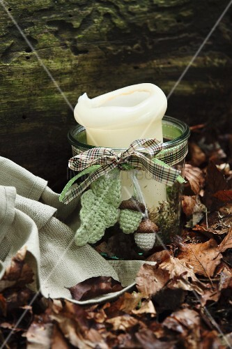 Autumn arrangement in woodland - candle lantern decorated with ribbon and crocheted acorns and leaf