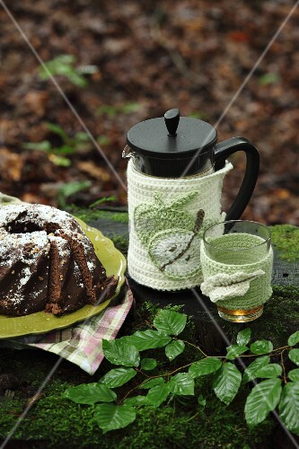 Crocheted coffee pot and glass warmer next to chocolate cake on plate in woodland