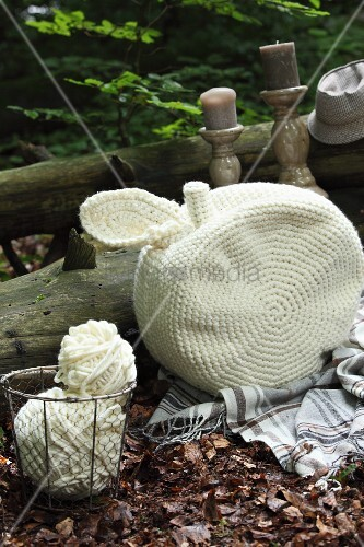 White, crocheted, apple-shaped cushion and ball of wool in wire basket on woodland floor