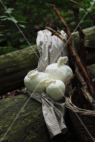 Crocheted apples of various sizes and wicker basket on tree trunk