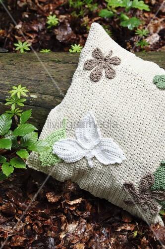 Gehäkelter Kissenbezug mit gehäkelten Blatt Applikationen auf Waldboden