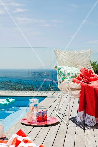 Refreshing drinks on wooden terrace next to white wicker chair next to pool; glass balustrade with sea view in background