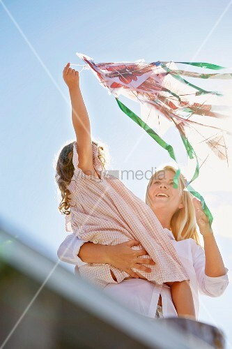 Mother and daughter playing with a kite