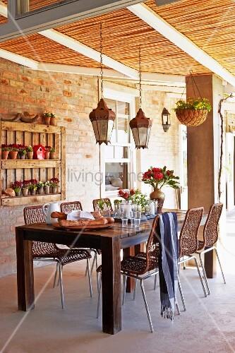 teakholz tisch und geflechtst hle auf berdachter terrasse. Black Bedroom Furniture Sets. Home Design Ideas