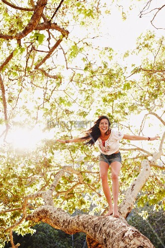 Young woman balancing in branches of a tree