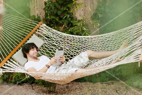 Young man lying in hammock holding tablet computer
