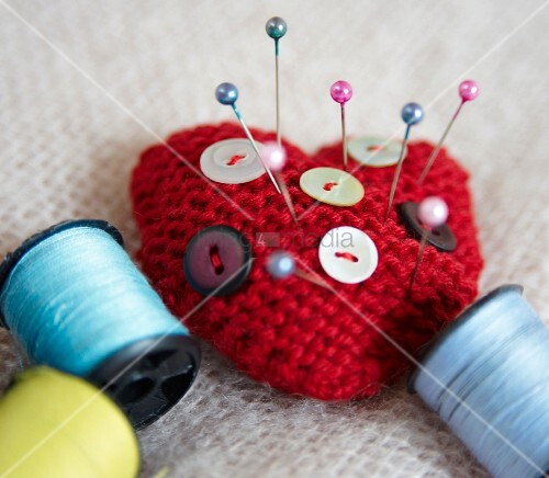 Heart-shaped pin cushion, buttons and thread