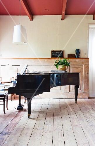 Schwarzer Konzertflügel auf Dielenboden und Vintage Holzverkleidung ...