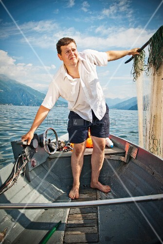 Fisherman standing in boat holding nets