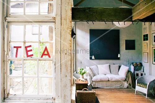 Gemütliches Weißes Polstersofa Mit Zwei Stehlampen Und Korbsessel Unter  Dunklem Gemälde In Renoviertem Fabrikgebäude Mit Shabby Sprossenfenstern