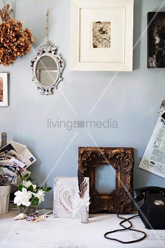 foto mit weissem bilderrahmen und spiegel an wand auf rustikalem holztisch vergoldeter. Black Bedroom Furniture Sets. Home Design Ideas