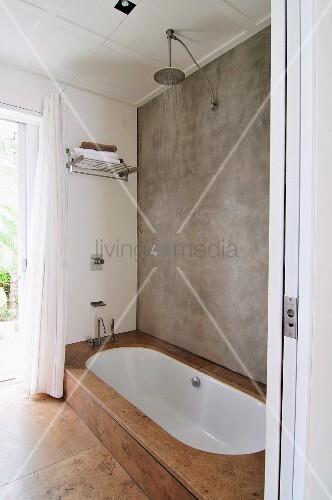 Fesselnd Reduziertes Badezimmer Mit Betonwand Und Regendusche, Eingelassene Weiße  Badewanne Mit Natursteinfliesen Verkleidet