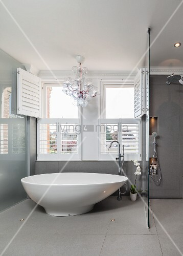 Free Standing Designer Bathtub In Front Of Open Wooden Louver Shutters And  Chandelier In Grey Bathroom With Rainfall Shower
