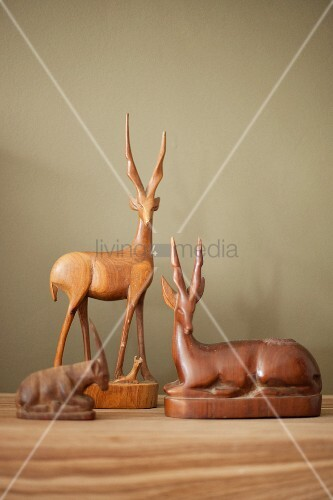 Wooden antelope figurines on wooden surface against wall painted pale grey