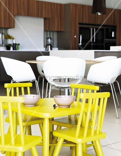 Yellow children's table and chairs in front of modern, white shell chairs in open-plan kitchen