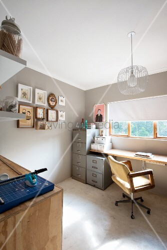 Paper cutter on wooden cabinet opposite desk below window with half-closed roller blind and grey metal filing cabinets in corner of room painted pale grey