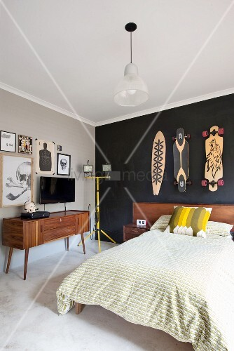 French bed with wooden headboard below skateboards hung on black-painted wall, TV on fifties sideboard below drawings on wall painted pale grey
