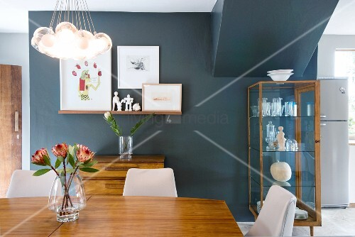 Glass vase of flowers on wooden table below pendant lamp with spherical glass lampshades and display case against black-painted wall