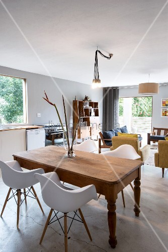 White, classic shell chairs around rustic wooden table; kitchen and lounge areas in background in open-plan, contemporary interior