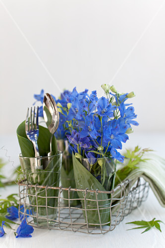 Larkspur and cutlery in glasses wrapped in hosta leaves