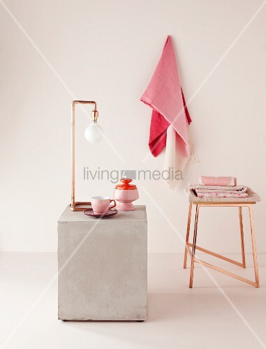 Purist lamp made from angled copper pipes and copper stool; crockery and fabrics in shades of pink