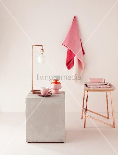 Puristische Lampe aus gebogenen Kupferrohren und Hocker in Kupfer; Geschirr und Tücher in Rosatönen
