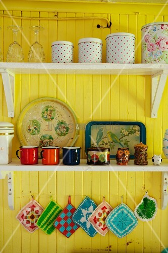 Storage jars and colourful, vintage, enamel mugs on shelves on yellow-painted wall