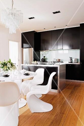 weisse designer schalenst hle und tisch auf dielenboden im hintergrund moderne theke und. Black Bedroom Furniture Sets. Home Design Ideas