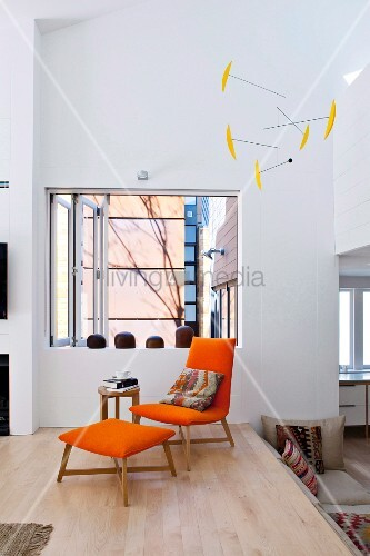Orangefarbener Sessel Mit Passendem Fussschemel Auf Podest Vor  Fensterartiger Öffnung; Mobile An Decke Hängend