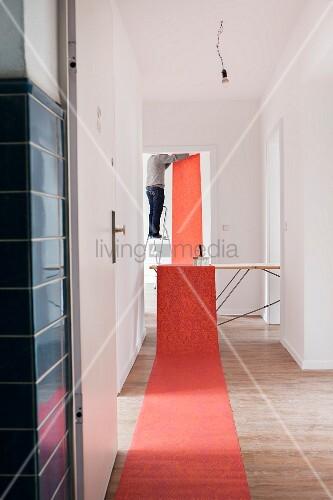 rotgemusterte tapete auf boden und tisch ausgerollt im hintergrund blick auf mann bei. Black Bedroom Furniture Sets. Home Design Ideas