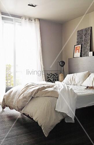 View through open door of double bed below window with airy curtains in bedroom