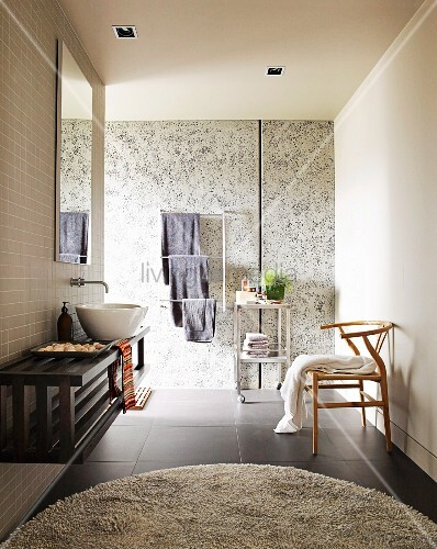 Modern bathroom with round rug on black tiled floor, floating washstand against wall & classic, wooden chair