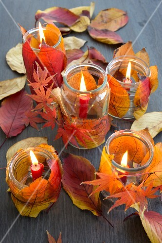 Candle lanterns decorated with autumn leaves