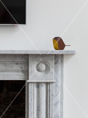 Small, minimalist wooden bird sitting on marble fire surround
