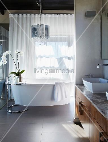 Modernes Bad   Seitlich In Nische Eingebauter Waschtisch Mit Unterschrank  Aus Holz, Freistehende Badewanne Vor Geschlossenem, Transparentem Vorhang  Am ...