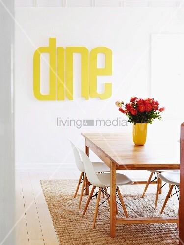 Blick auf Essplatz - Dahlienstrauss auf Holztisch, weisse Klassiker Schalenstühle auf Sisalteppich, im Hintergrund gelb lackierte Buchstaben an Wand