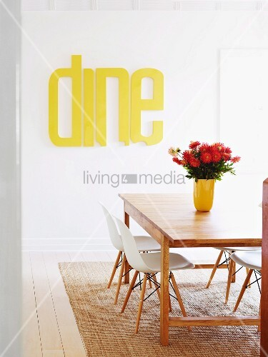 Dining area - vase of dahlias on wooden table, white classic shell chairs on sisal rug and bright yellow letters painted on wall