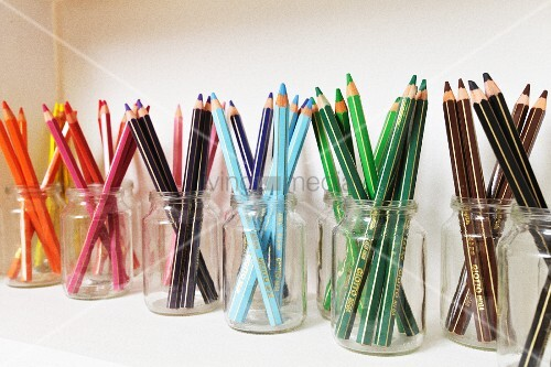 Coloured pencils arranged by colour in jars on wall-mounted shelf