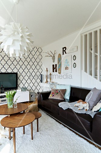 Designer artichoke lamp and set of retro side tables in front of black leather sofa; wallpaper with Oriental tile motif and vintage ornaments in background