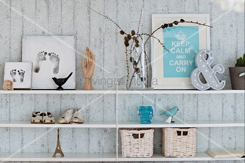 Baby's footprints, booties, framed motto and ornaments on shelves on exposed concrete wall