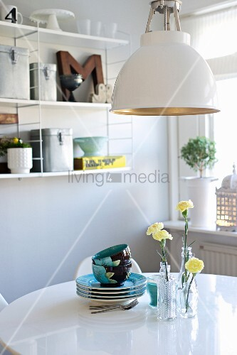 Retro lamp above crockery and yellow carnations in glass vases on white dining table