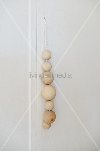Wooden balls of different sizes threaded on cord as handle of cupboard door