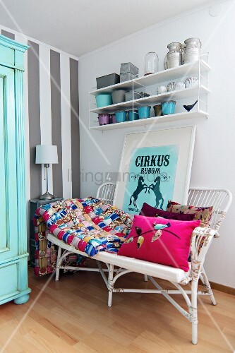 Patchwork blanket, cushions and framed circus poster on wicker bench below pots on floating shelves; accent wall with wide, pale grey stripes