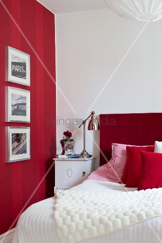 Gerahmte Bilder An Rot Gestreifter Wand, Daneben Ein Bett Mit Rotem Kopfteil  Und Leuchte Im Retrostil Auf Nachtkasten