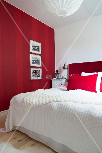 Gerahmte Bilder An Rot Gestreifter Wand, Daneben Ein Bett Mit Rotem Kopfteil