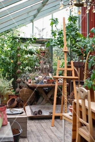 staffelei vor pflanzent pfen und gartenzubeh r in gew chshaus bild kaufen living4media. Black Bedroom Furniture Sets. Home Design Ideas